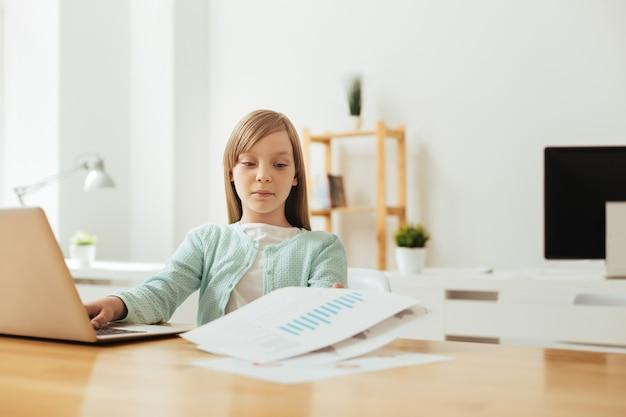 Трудолюбивая милая милая девушка сидит за столом и работает над своим школьным заданием