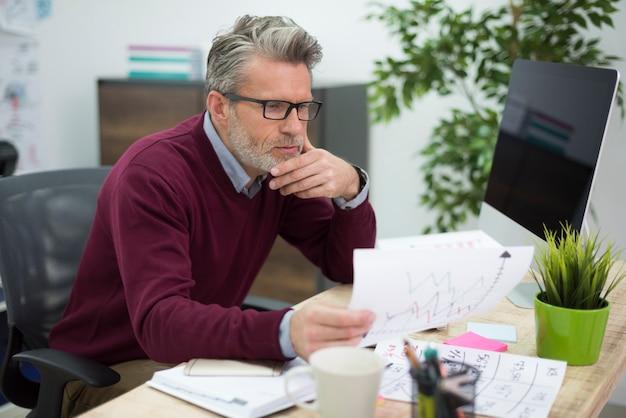 Uomo laborioso che legge alcuni documenti importanti