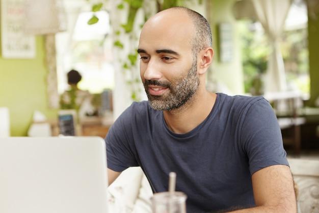 Трудолюбивый мужчина с вдохновенной улыбкой смотрит на экран своего портативного компьютера во время просмотра видео онлайн.
