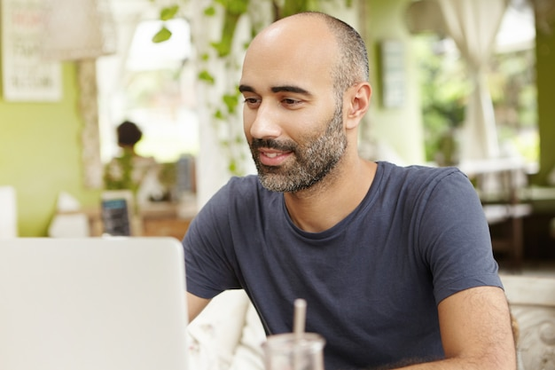 Hardworking man with inspired smile looking at screen of his generic laptop while watching video online.