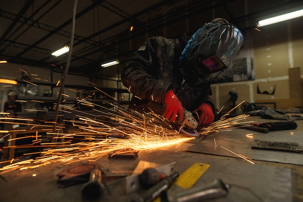 Трудолюбивый человек с защитной маской работает с электрическим шлифовальным инструментом на стальной конструкции на заводе во время полета искры
