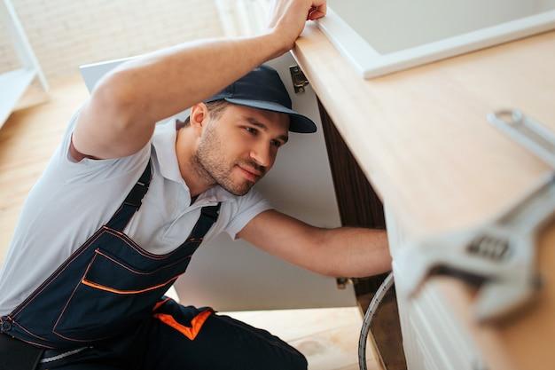 Hardworking plumber look under sink in kitchen