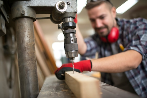 Falegname professionista laborioso che fora materiale in legno con trapano verticale