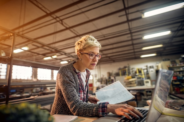 Hardworking professional engineer short hair woman working on a laptop while holding blueprint in another hand in the sunny workshop