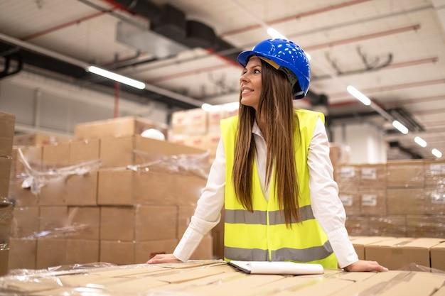 ヘルメットと反射ジャケットを持った勤勉なプロの女性労働者またはマネージャーは、大きな倉庫で脇を見ている段ボール箱に寄りかかった