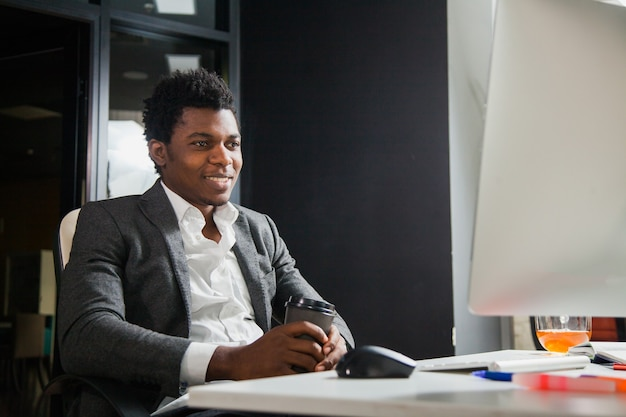 사무실에서 열심히 일하는 웃는 남자는 컴퓨터 모니터를 봐