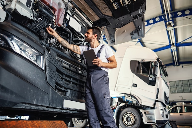 Hardworking tattooed bearded mechanic leaning on truck and checking on motor while standing in garage of import and export firm.