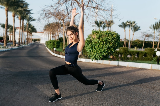 Hardworking young attractive woman at stretching on street with palm trees. tropical city, sportive lifestyle, training, motivation, outwork, fashionable model, healthy life