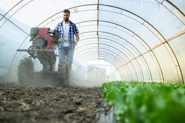 有機食品農場で新しい苗のための土壌を準備するためにモーターカルチベーターを操作する勤勉な若い農夫