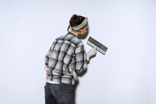 Трудолюбивая молодая девушка-строитель облицовывает стены шпателем, делает ремонт в квартире