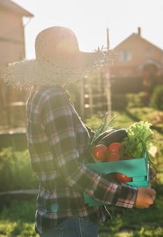 麦わら帽子の勤勉な若い女性の庭師は、晴れた夏にトマトの収穫箱を拾います