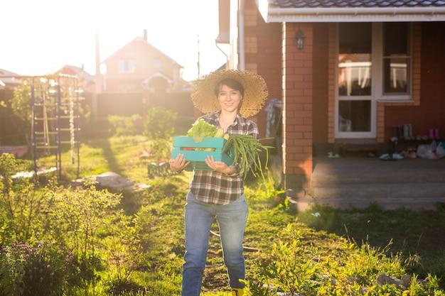 麦わら帽子の勤勉な若い女性の庭師は、野菜の収穫箱を拾います
