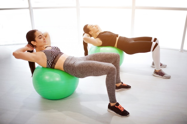 Hardworking young women lying on green fitballs and do abd workout. they keep hands behind head. models exersiting at window
