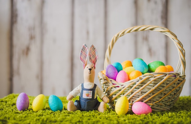 Hare sitting on the grass with easter eggs