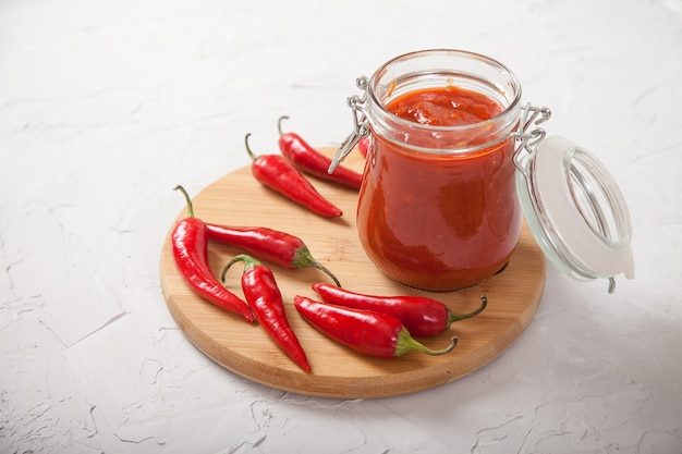 Harissa in a glass jar on a wooden stand and hot chili peppers.