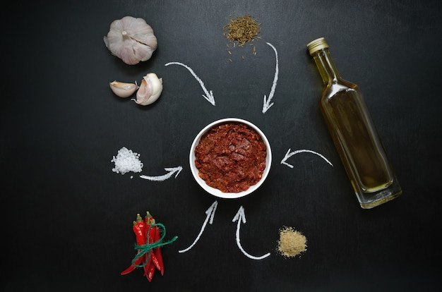 Harissa ingredients for cooking hot chilli red pepper, coarse sea salt, garlic, cumin zira, olive oil, ground coriander on a dark slate table. adjika, muhammara.
