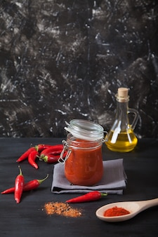 Harissa spicy herb in a glass jar stands on a gray linen napkin, a wooden spoon with spices, oil and chili pepper. copy spaes,