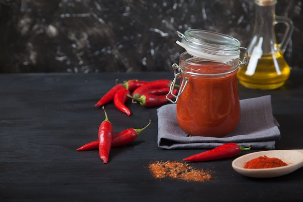 Harissa spicy herb in a glass jar stands on a gray linen napkin, a wooden spoon with spices, oil and chili pepper.