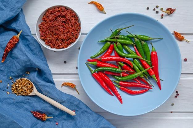 Паста с соусом из острого перца чили harissa, традиционная тунисская, марокканская, арабская кухня аджика, специи с перцем чили и свежий красный и зеленый перец чили в синей тарелке, над белым столом