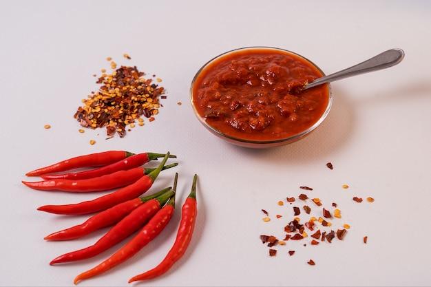 Самодельная красная паста harissa, специи перца чили и свежие красные перцы чили.