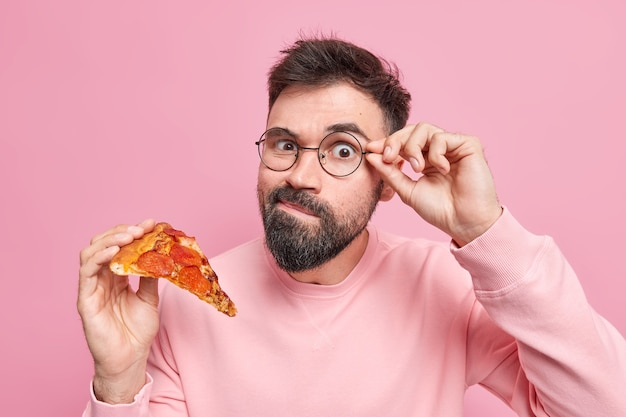 Harmful delicious food. handsome bearded man has tasty snack keeps hand on rim of spectacles holds slice of appetizing italian pizza has harmful unhealthy eating habits