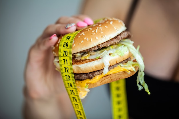 Harmful food. the choice between malicious food and sport. beautiful young girl on a diet. the concept of beauty and health.