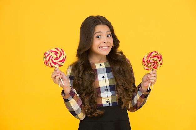 有害な食品。お菓子に夢中。砂糖中毒。甘いお菓子で幸せな子供。ロリポップキャンディー黄色の背景を保持している子供の子供。お菓子と幸せな子供。学校の栄養。カロリーとエネルギー。