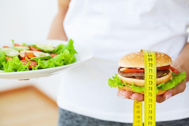 유해한 음식, 노란색 측정 테이프 옆에 뚱뚱한 햄버거.