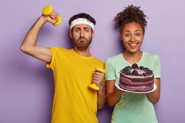 유해한 영양 및 스포츠 개념. 동기 부여 된 남자는 달콤한 케이크를 먹기를 거부합니다