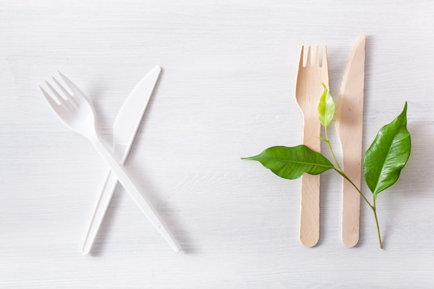 Harmful plastic cutlery and eco friendly wooden cutlery. plastic free concept