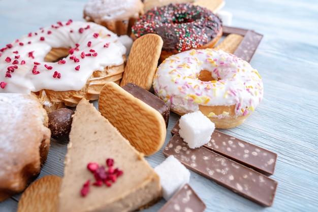 Вредные сладкие продукты на синем деревянном фоне