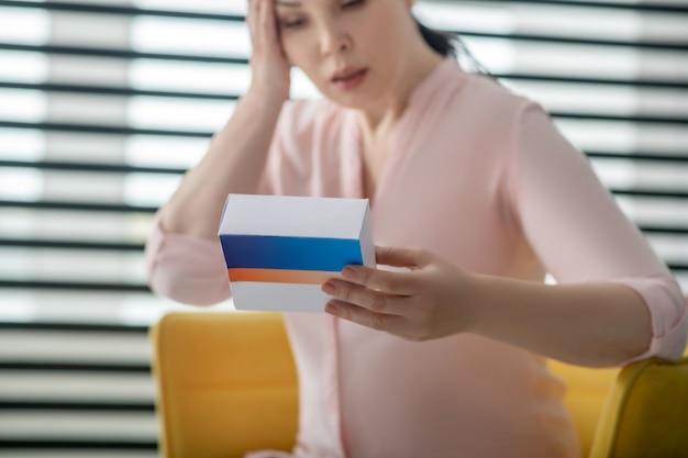 Harmones, женское здоровье. внимательная серьезная женщина в светло-розовой блузке с коробкой таблеток в руке, другая рука у головы.
