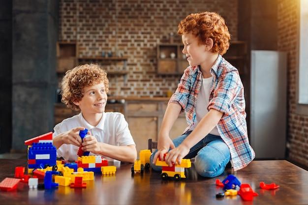 調和のとれた家族関係。ビルディングブロックセットで遊んだり、一緒に過ごした時間を楽しんだりしながら、お互いを見て、うわさ話をしている子供たちを笑顔にします。