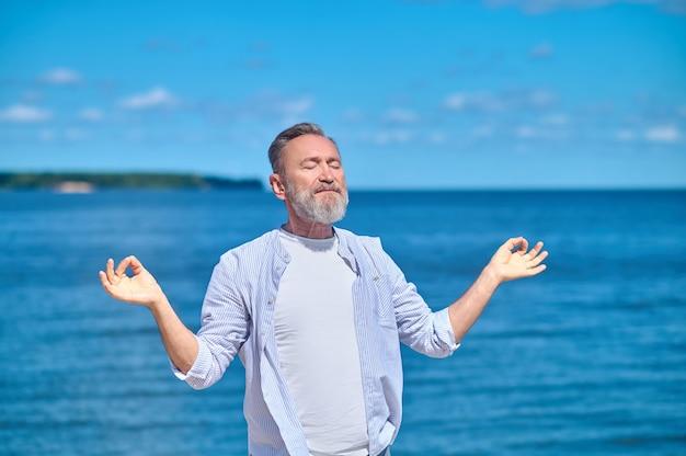 Гармония. взрослый бородатый мужчина с закрытыми глазами в легкой футболке и рубашке выполняет гьяна мудру возле моря в солнечный день