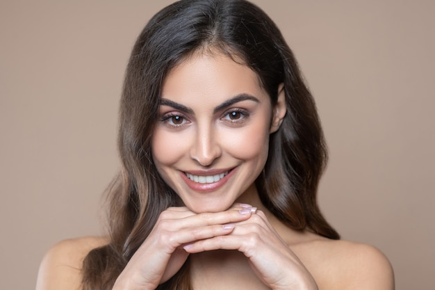 Harmony. happy young long-haired woman with beautiful smile and bare shoulders on beige background