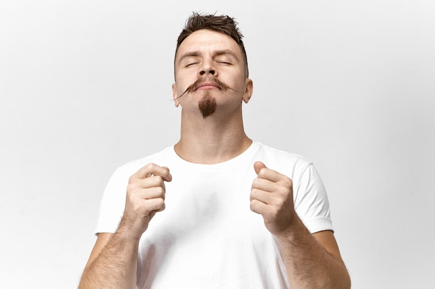 Concetto di armonia, pace ed equilibrio. studio shot di bello ed elegante giovane maschio vestito di t-shirt bianca chiudendo gli occhi, avendo calma compiaciuta espressione facciale, meditando o ascoltando bella musica
