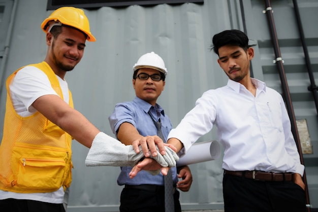 Harmony team of engineering manager, field engineer, foreman gather hands together