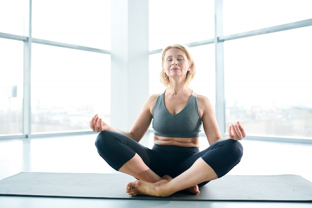 In harmony. woman on mat meditating next to a large window