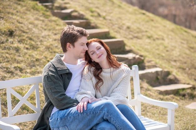調和。目を閉じてかわいい笑顔の女性を抱き締める若い成人男性は、屋外で休んで幸せです