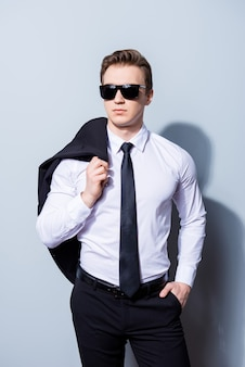 Harsh agent, standing on a pure space. he looks stunning and severe, wearing formal clothes and sunglasses, holds jacket and has a hand in a pocket