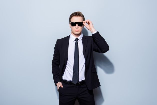 Harsh agent, standing on a pure space. he looks stunning and severe, wearing suit and sunglasses, fixing them and has a hand in a pocket