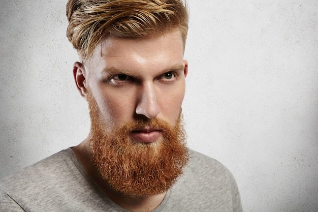 Harsh caucasian man with perfect light skin looking ahead like a brave hero. his fringe is carefully styled and temples are shaved, well-trimmed ginger beard fits him well.