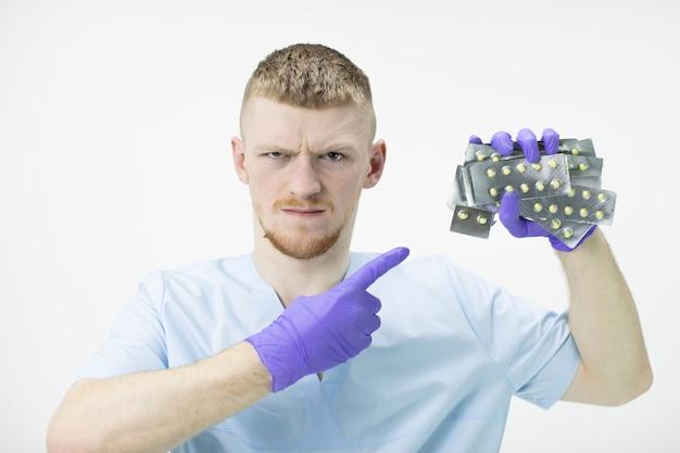 Суровый медицинский работник с сердитым выражением лица указывает на блистеры