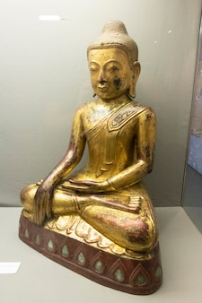 Hartlepool, u.k - july 27, 2021: the national museum of the royal navy, in the north of england. wooden golden budha statue display cabinet