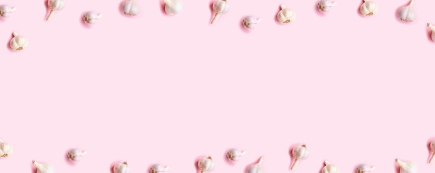 Harvest concept. bulbs of garlic frame on a pink wooden background