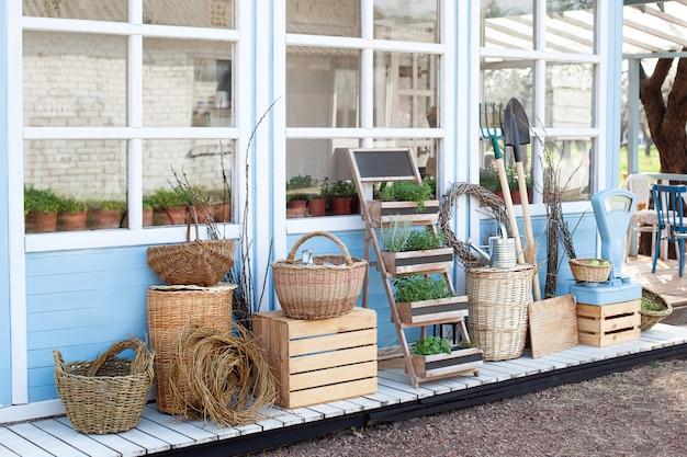 収穫のコンセプト。青いカントリーハウスの壁のそばにある庭の道具の横にあるickerのバスケット。カントリーハウスの中庭の装飾。ガーデニングのコンセプト。たっぷりの秋の収穫。