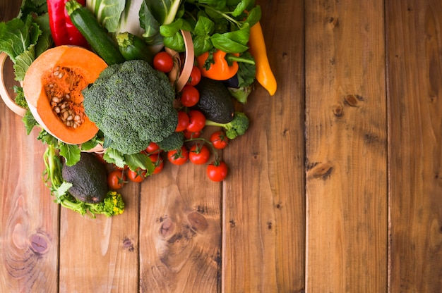 Harvest. food or healthy diet concept. big basket with different fresh farm vegetables, pumpkin, broccoli, chard, avocado and tomatoes. copy space. selective focus. top view