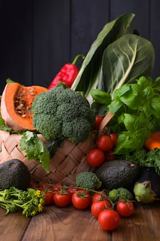 Harvest. food or healthy diet concept. big basket with different fresh farm vegetables, pumpkin, broccoli, chard, avocado and tomatoes. copy space. selective focus.