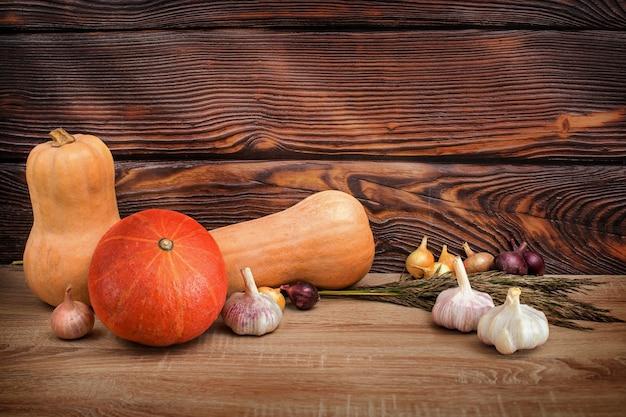 秋の野菜のカボチャ、リンゴ、トウモロコシ、スカッシュ、ズッキーニ、タマネギの収穫。自然なエコ食品のコンセプト。