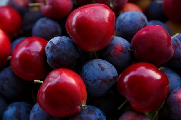 熟した青い梅と赤いリンゴの収穫がクローズアップ